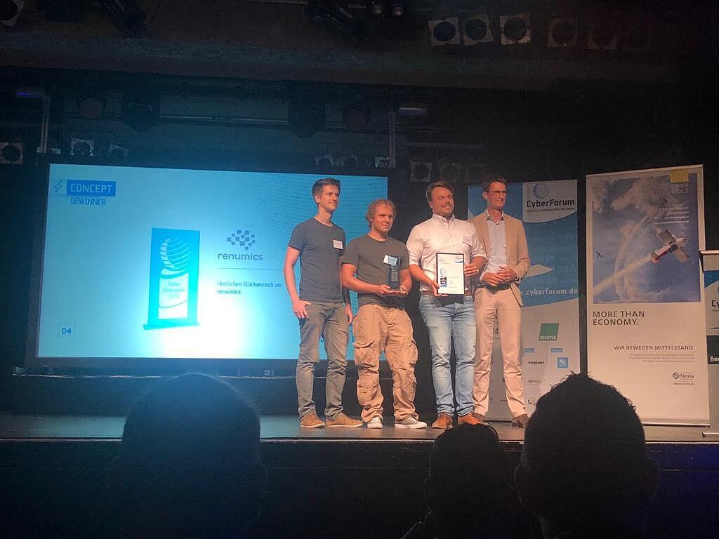 vier Personen die auf der Bühne stehen wo zwei davon Auszeichnungen halten