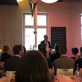 Personen die in einem Raum versammelt sind und einem Mann im Hintergrund bei einer Rede zuhören