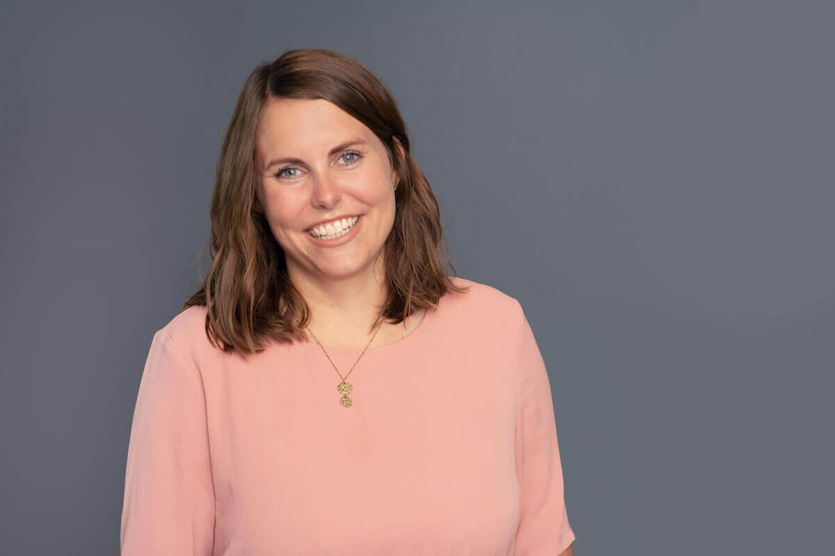 Frau vor grauem Hintergrund, schaut lächelnd in die Kamera