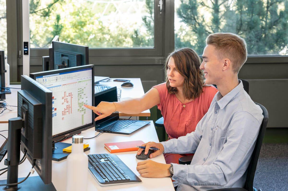 Eine Mitarbeiterin zeigt auf einen Bildschirm, um einem anderen etwas zu erklären.