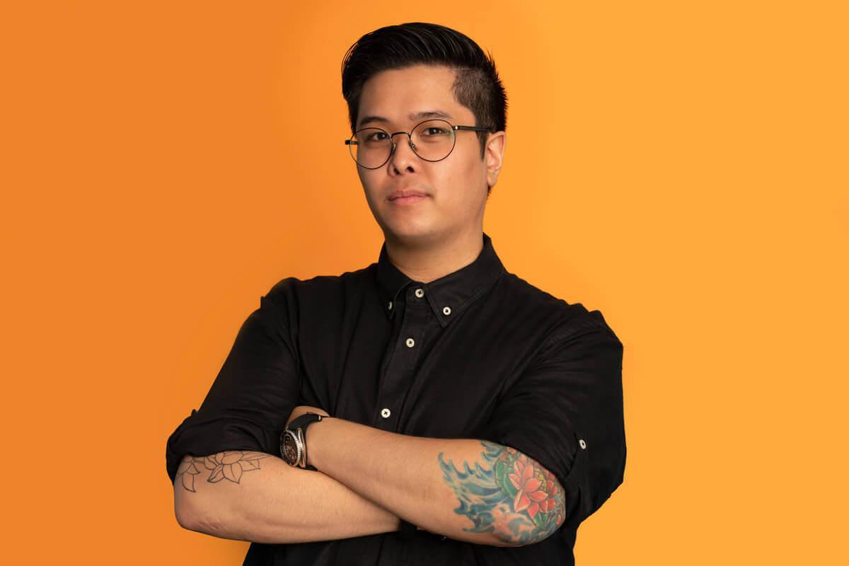 Asiatischer Mann steht mit verschränkten Armen vor einem gelben Hintergrund
