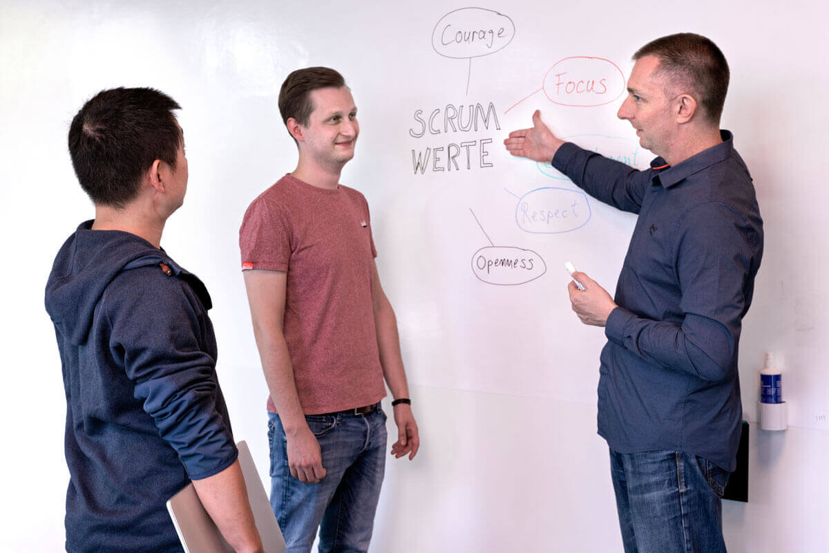 Drei Mitarbeiter stehen um ein White Board. Dort zu sehen sind die Scrum Werte, auf die ein Mitarbeiter zeigt.