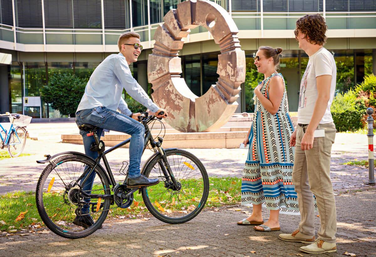 Eine Frau und zwei Männer außen vor dem Sovendus Gebäude. Ein Mann sitzt auf einem Fahrrad
