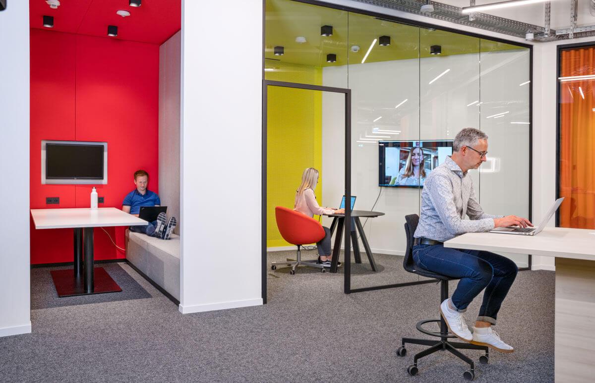 Verschiedene Arbeitsbereiche, Meetingraum mit Bildschirm, Sitzecke mit Bildschirm und offener Arbeitsbereich in allen Bereichen sitzen arbeitende Mitarbeiter