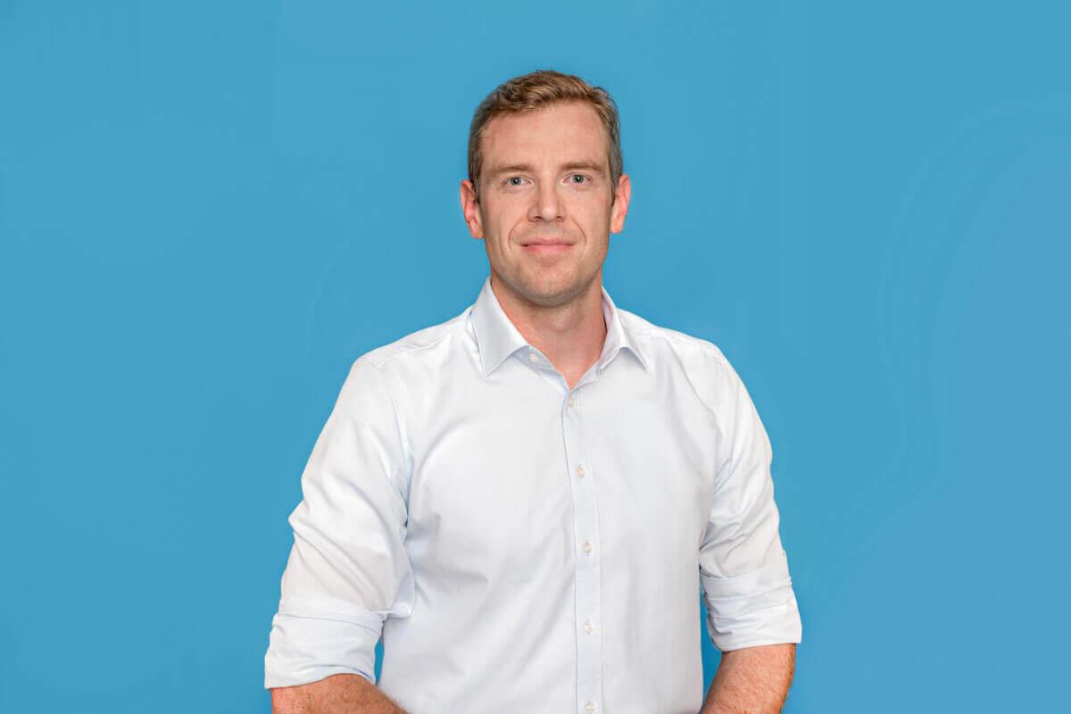 Mann vor hellblauem Hintergrund, schaut lächelnd in die Kamera