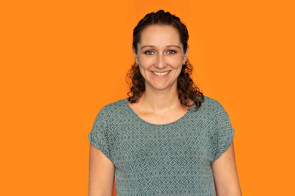Frau vor orangem Hintergrund, schaut lächelnd in die Kamera