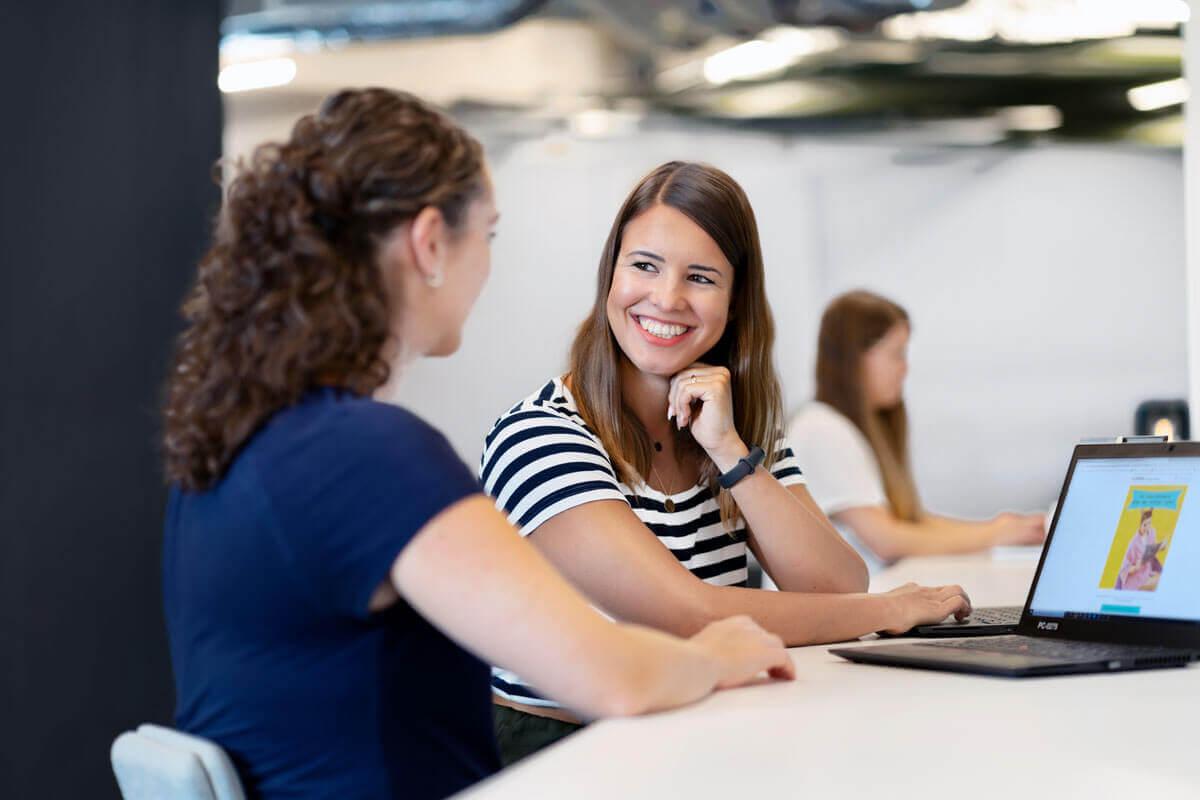 Zwei Mitarbeiterinnen die sich über ein Bild auf einem Laptop unterhalten