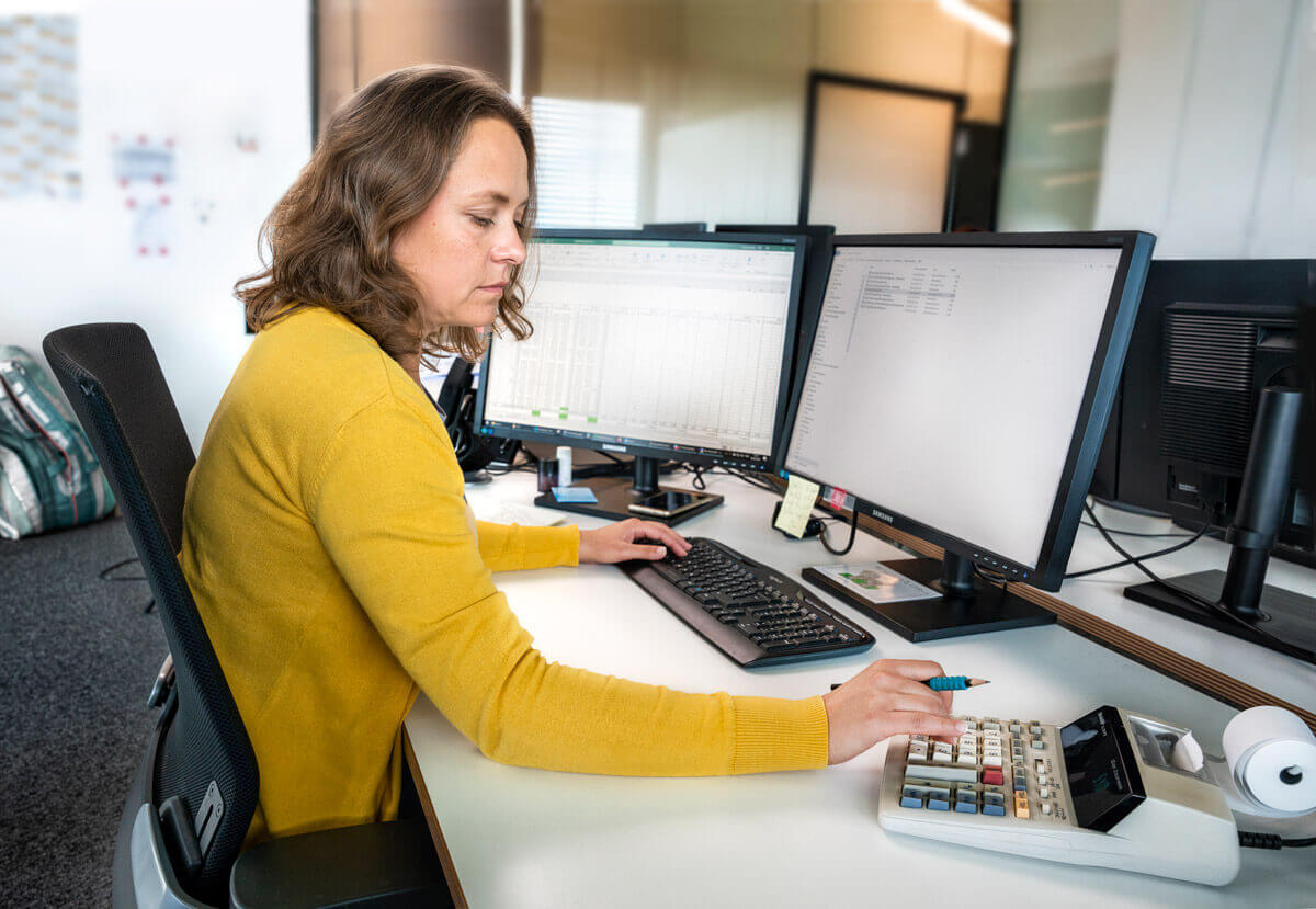 Eine Mitarbeiterin von Finance, die Zahlen aus einer Excel Liste in Boniergerät tippt