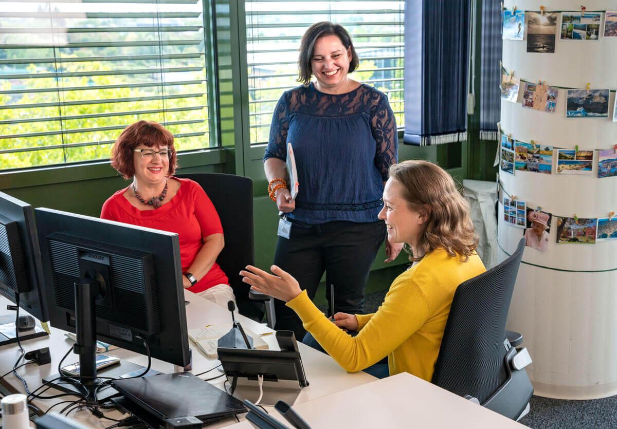 Three Finance employees talking at their desks