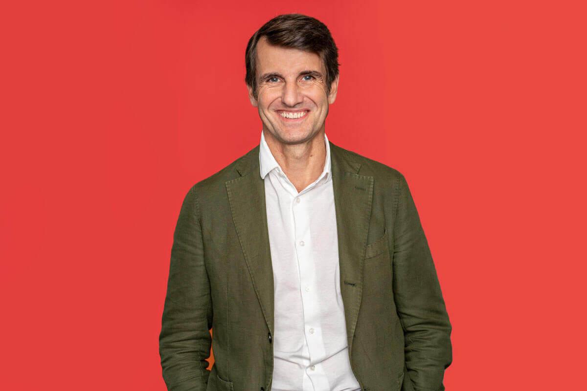 Mann vor rotem Hintergrund, schaut lächelnd in die Kamera