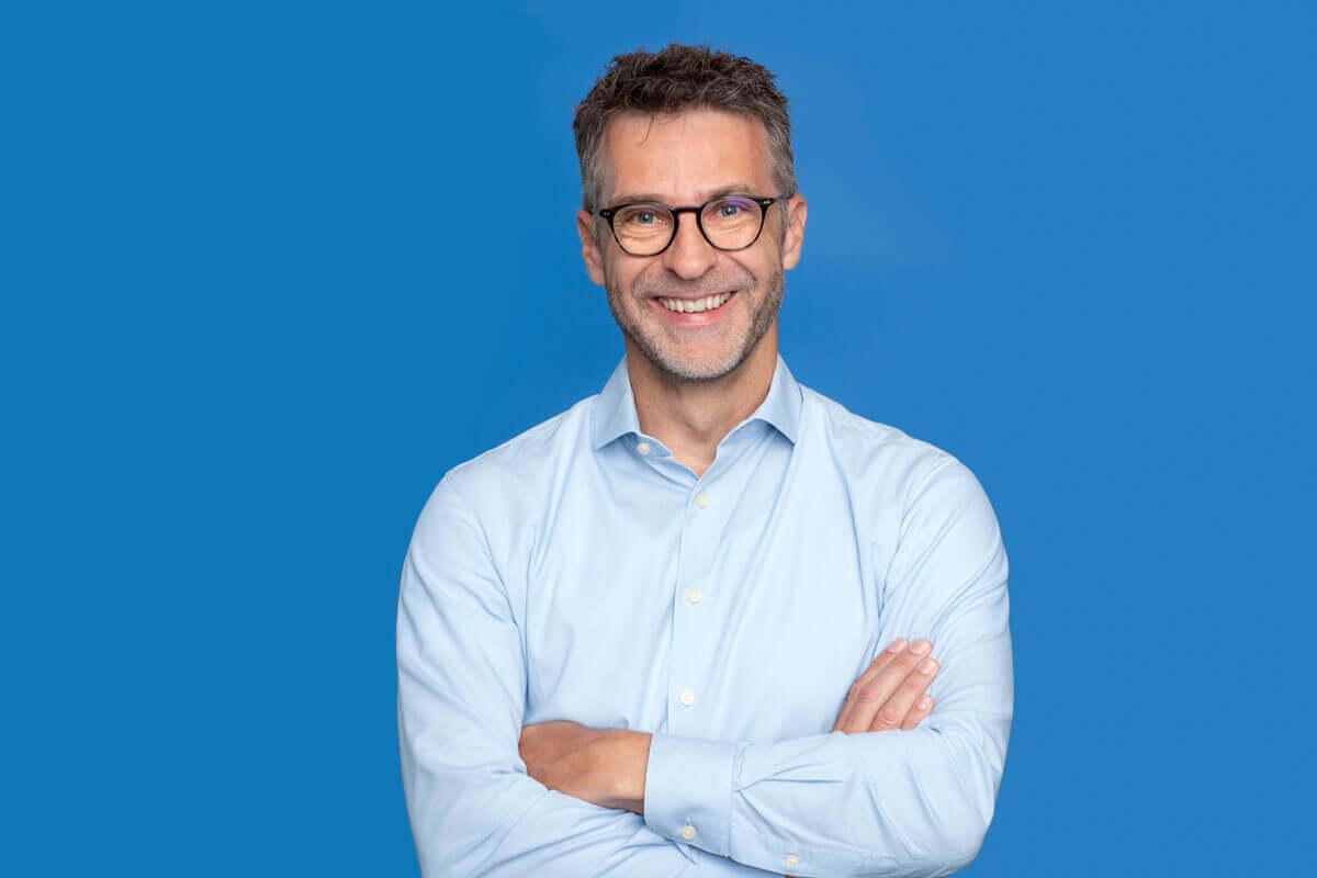 Mann vor blauem Hintergrund, schaut lächelnd in die Kamera