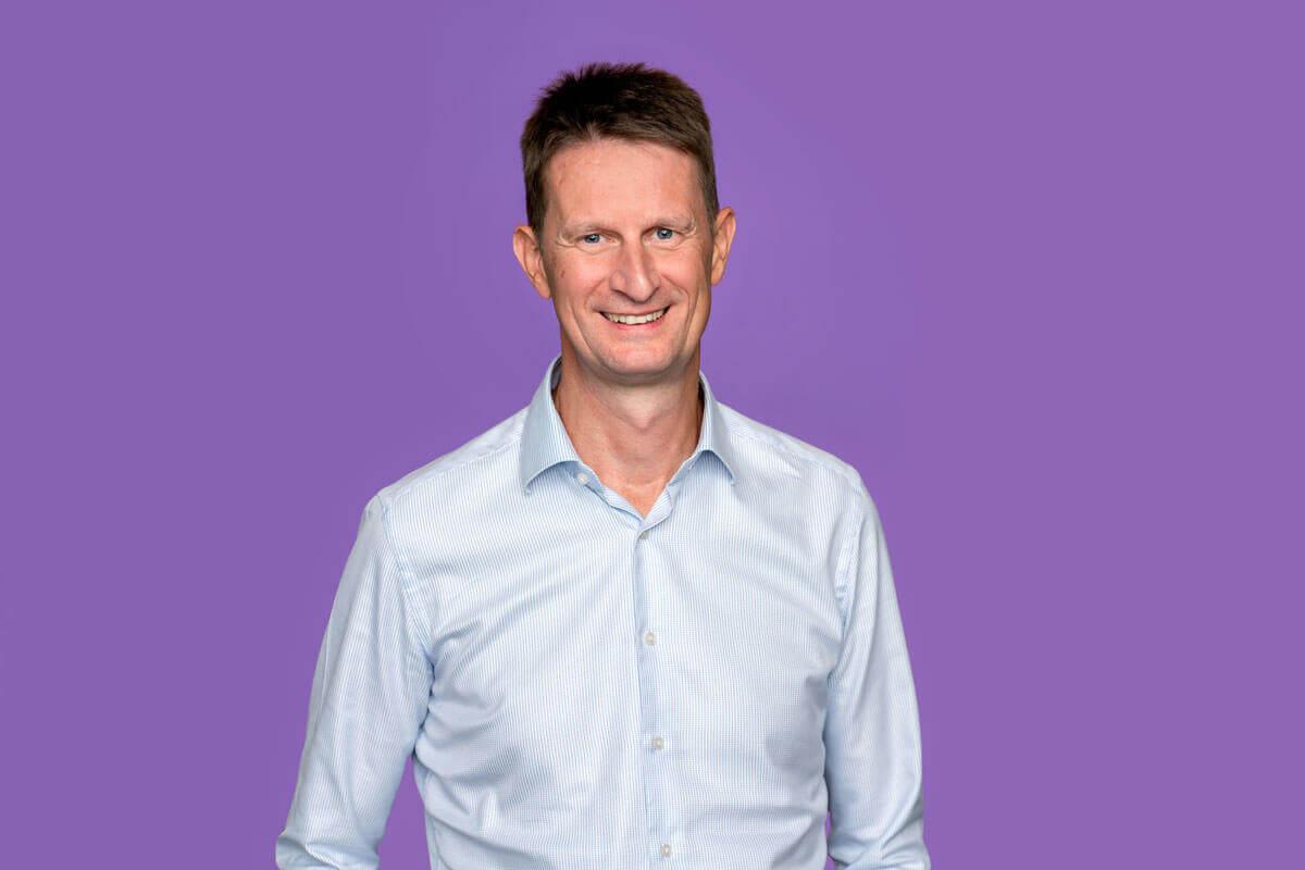 Mann vor lila Hintergrund, schaut lächelnd in die Kamera