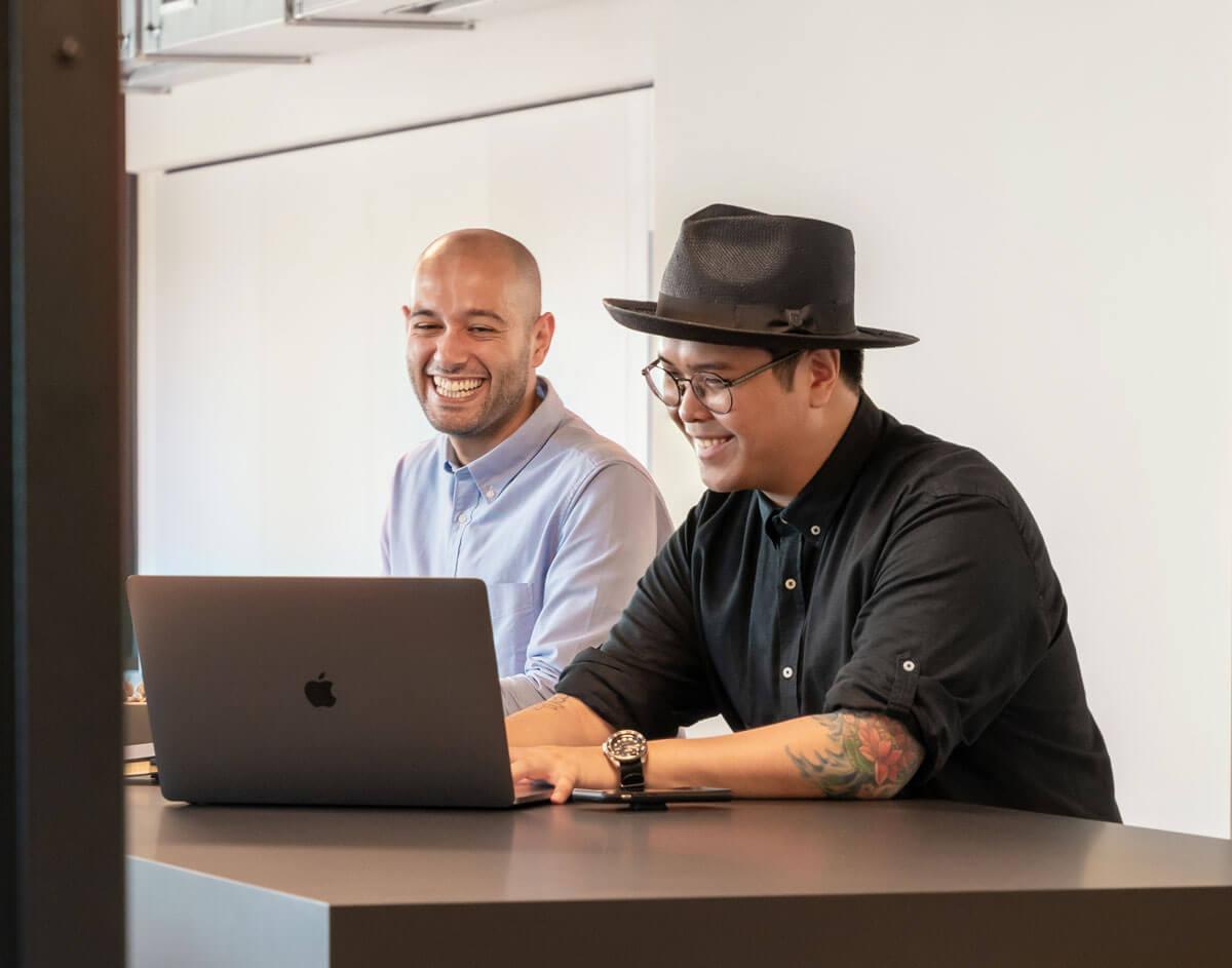 Zwei Männer sitzen lachend vor einem Laptop