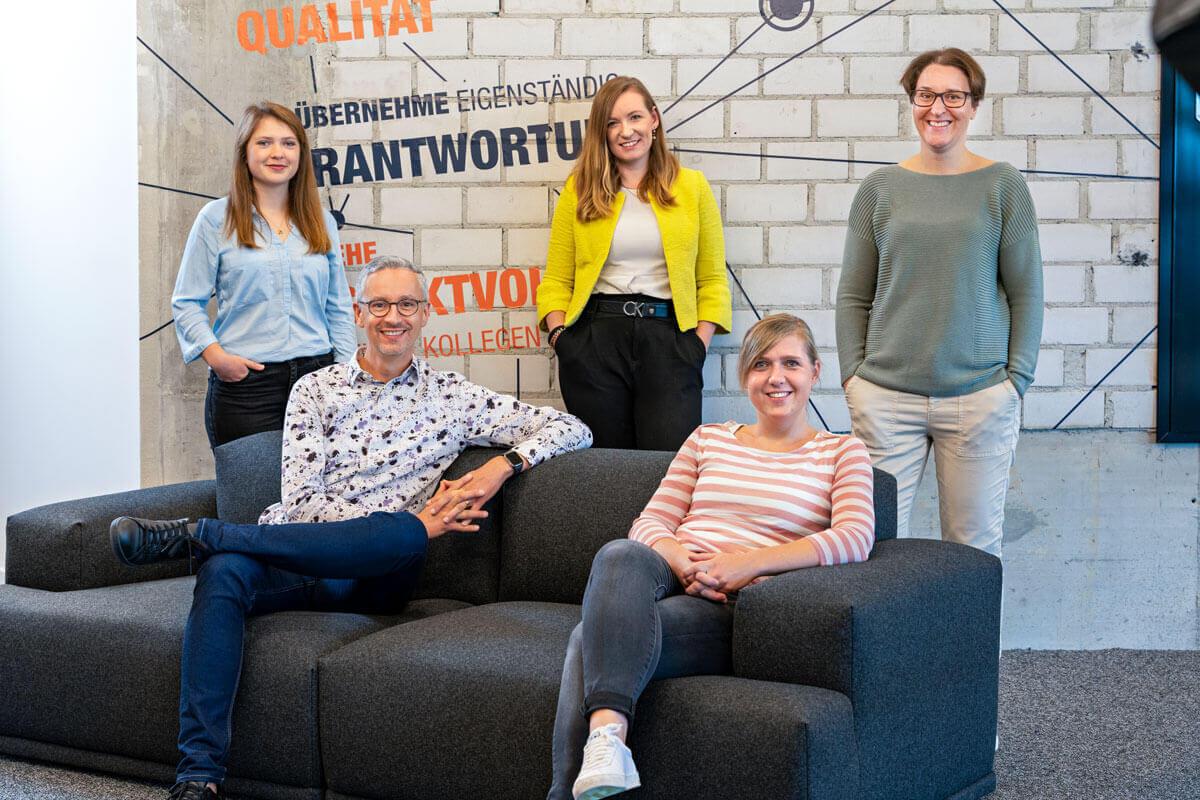 Das HR-Team sitzt und steht um ein Sofa herum und lächelt