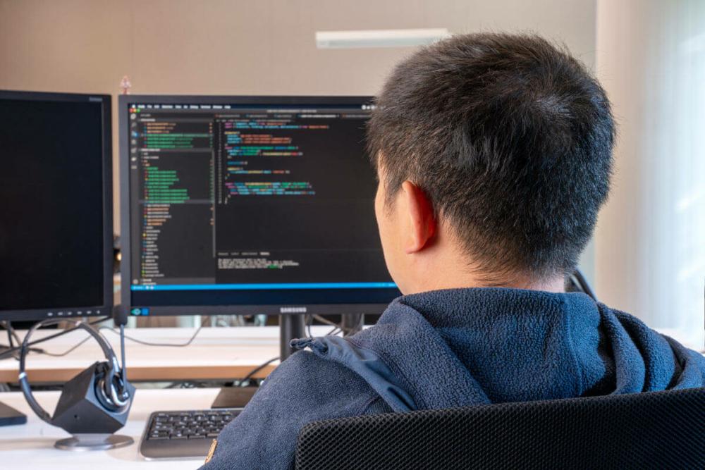 Mann vom IT Team sitzt am Schreibtisch vor seinem Bildschirm
