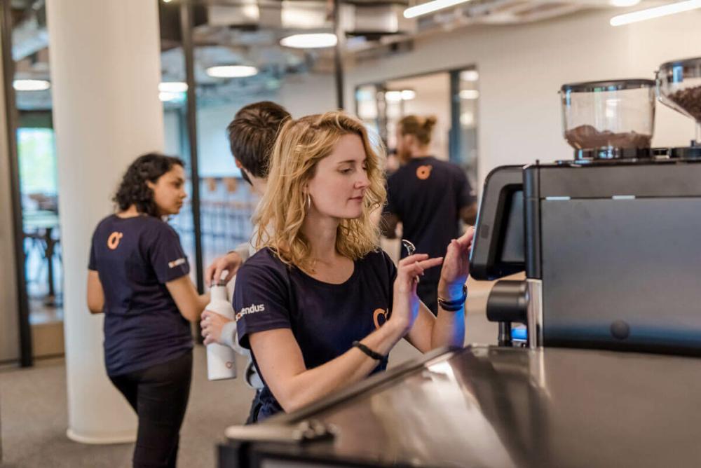 Frau im Vordergrund bedient die Kaffeemaschine, im Hintergrund weitere Mitarbeiter im Gespräch.