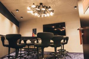 Ein Meetingsraum im Sovendusbüro, ausgestattet mit Whiteboards, Bildschirm und hochwertigen Möbel, sowie einer ausgefallenen Deckenlampe.