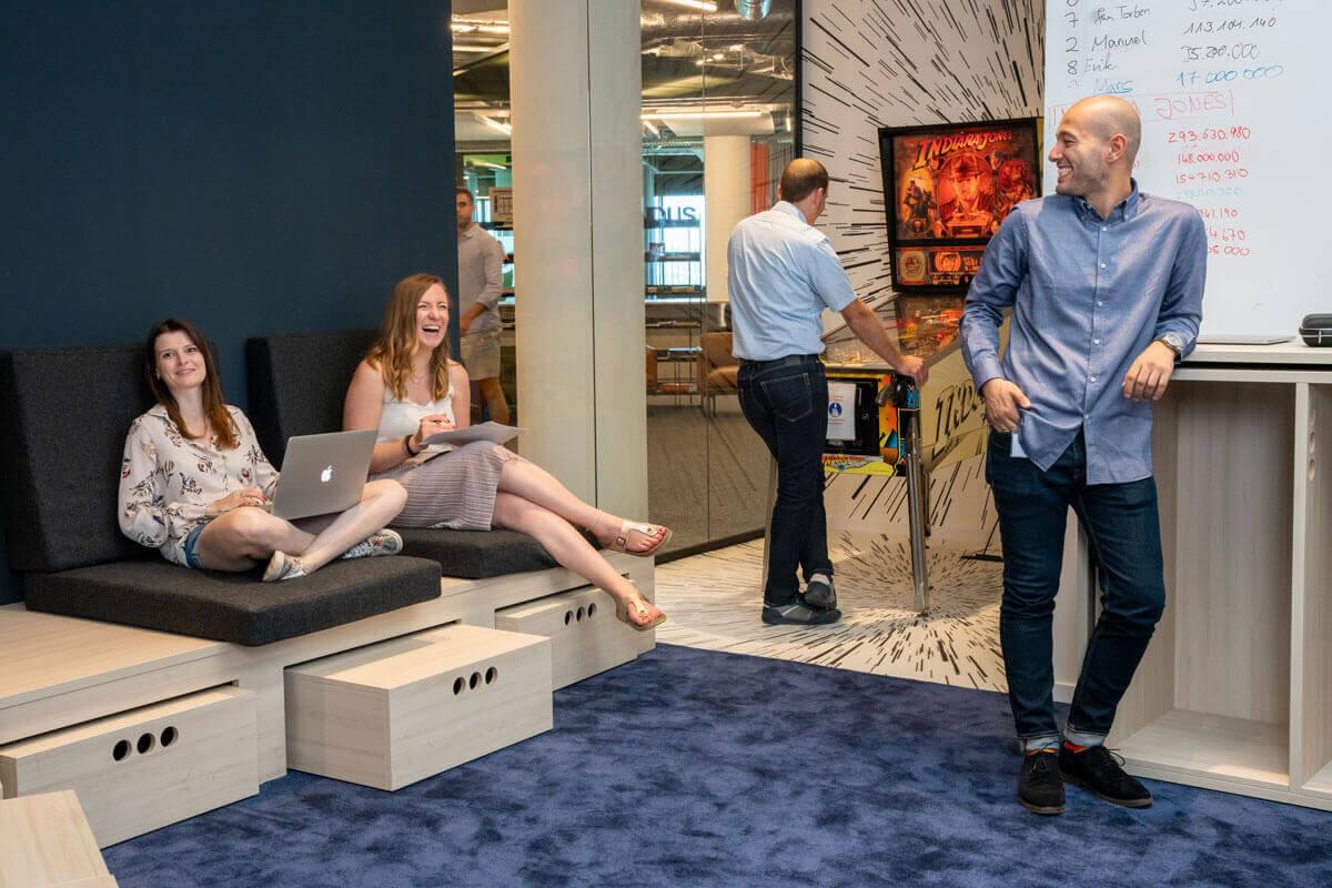 Gruppe von Menschen die sich anlachen, im Hintergrund Mann an einem Flipperautomat
