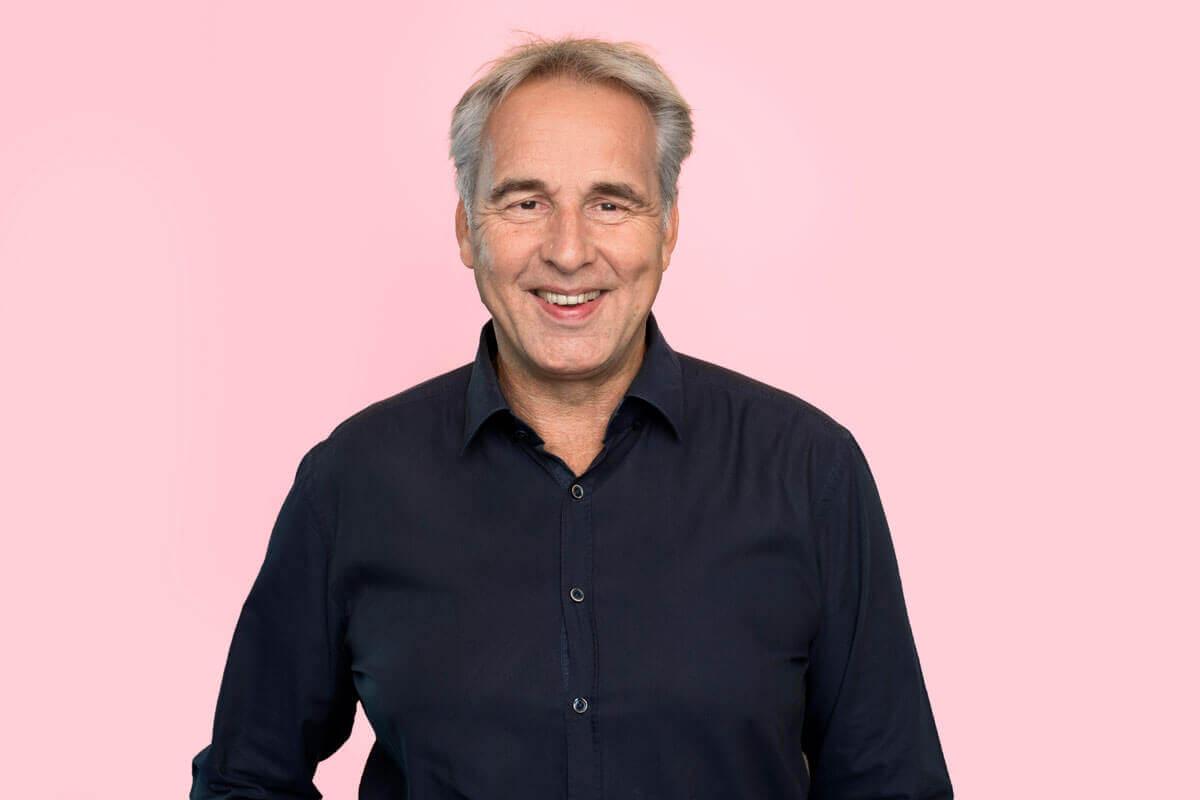 älterer Mann vor rosa Hintergrund, schaut lächelnd in die Kamera