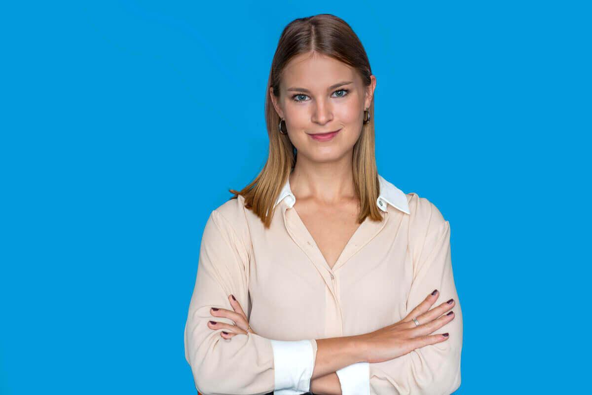 Frau vor blauem Hintergrund, schaut lächelnd in die Kamera