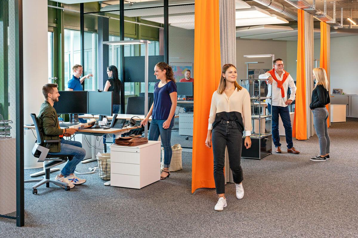 Aufnahme des Büros von Sovendus. Mehrere Mitarbeiter, im Gespräch oder bei der Arbeit, sind zu sehen.