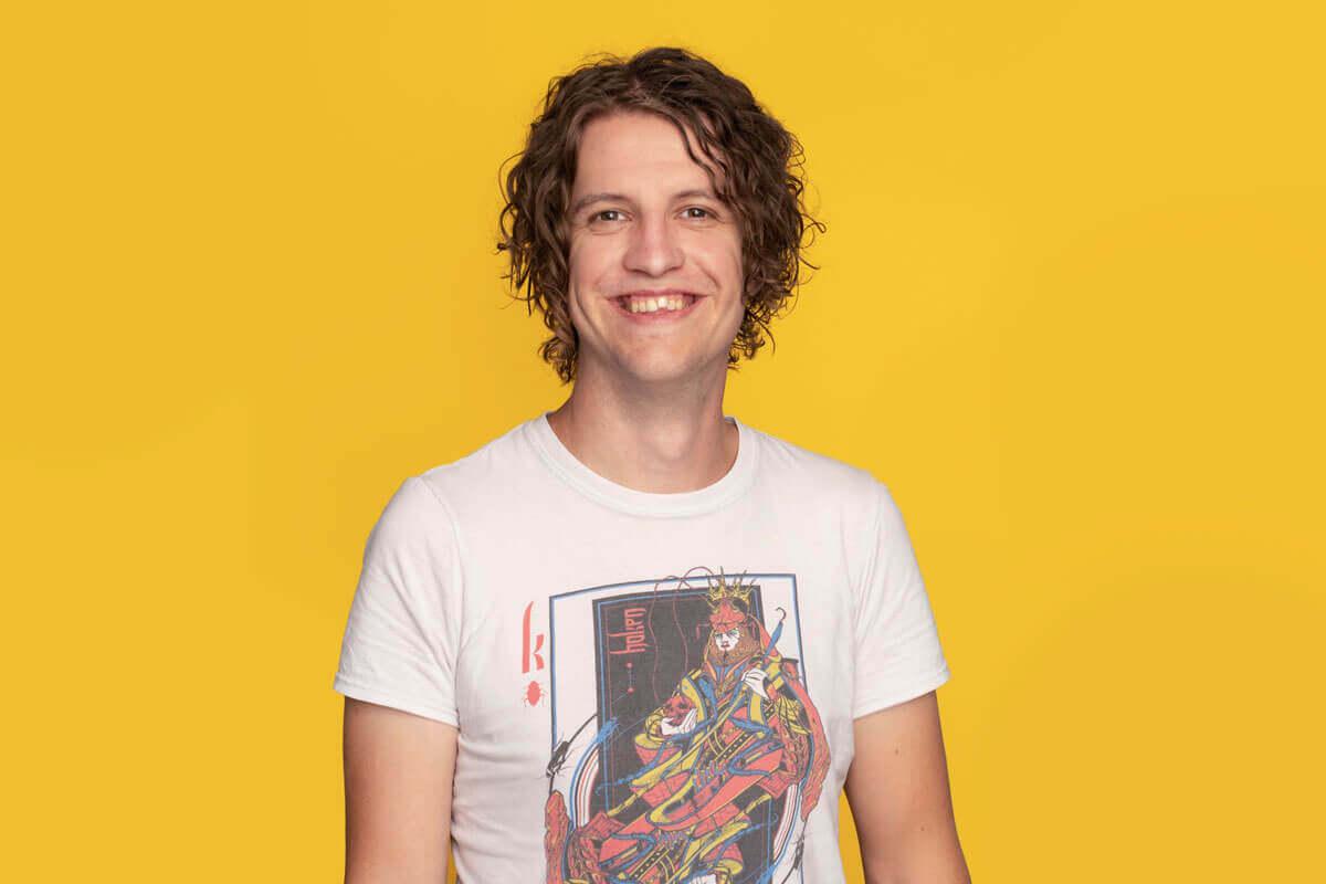 Mann vor gelbem Hintergrund, schaut lächelnd in die Kamera