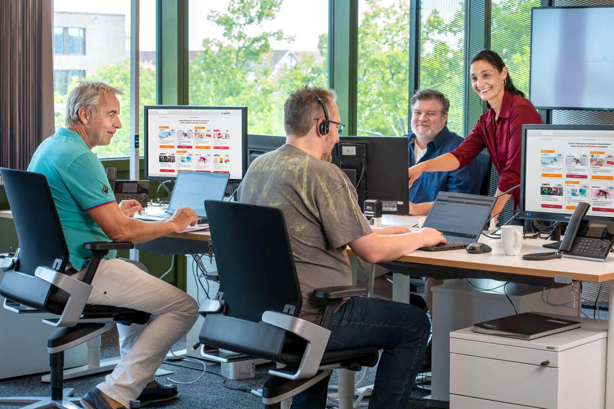 Vier Mitarbeiter aus der Sales Abteilung bei der Arbeit.