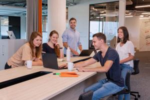 5 Werkstudenten sitzen an einem großen Tisch. Um sie herum stehen Kaffeetassen und Notziblöcke. Die Blicke sind auf den vordersten Laptop gerichtet.