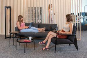 Zwei Frauen auf einer Couch und einem Sessel arbeiten an ihren Laptops.