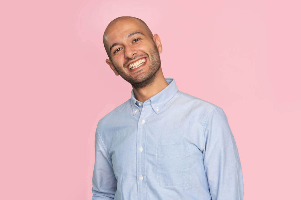 Grinsender Mann vor rosa Hintergrund, schaut lächelnd in die Kamera