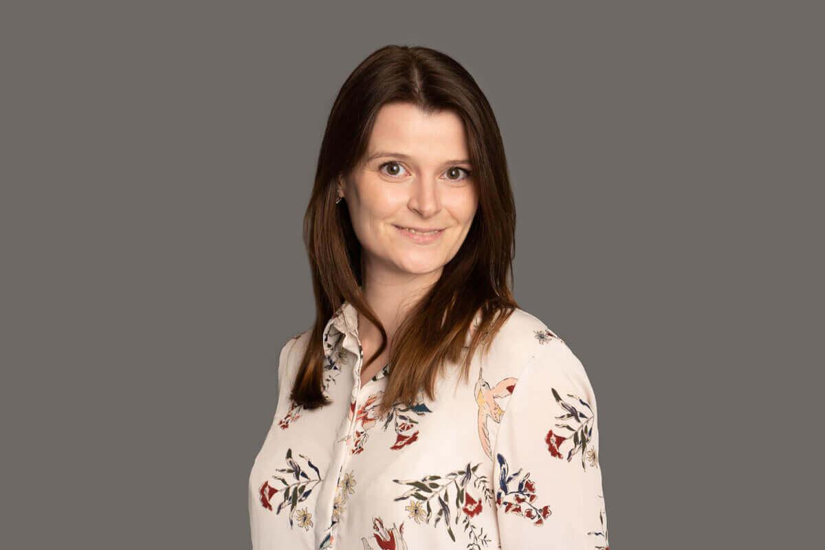 Lächelnde Frau mit gemusterter Bluse steht vor einem grauen Hintergrund, schaut lächelnd in die Kamera