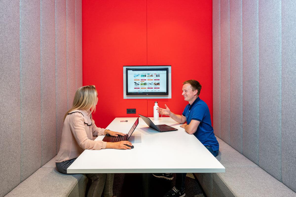 Das Team von voucher Products bei einem Gespräch in einem Meetingraum. Beide haben einen Laptop vor sich stehen und unterhalten sich angeregt. Im Hintergrund ist ein Bildschirm mit der Gutscheinauswahlseite zu sehen.