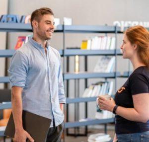 zwei Sovendus Mitarbeiter unterhalten sich. Junger Mann links trägt einen Laptop, die Gesprächspartnerin hält eine Kaffeetasse