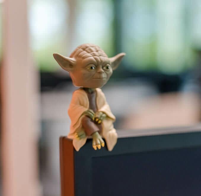 Yoda-Figur, die auf einem Bildschirm sitzt.