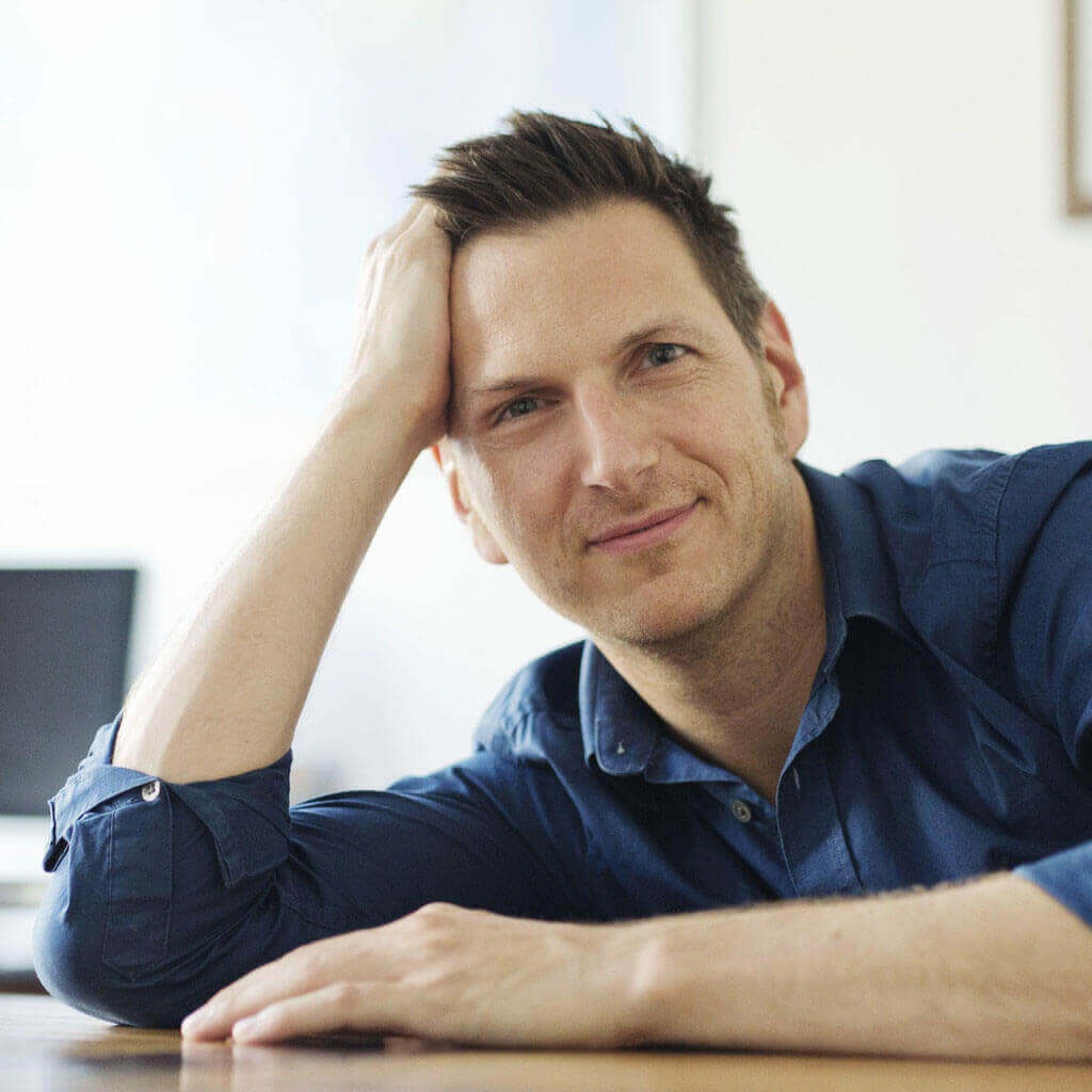 Porträtfoto von einem Mann, der sich auf Tisch abstützt