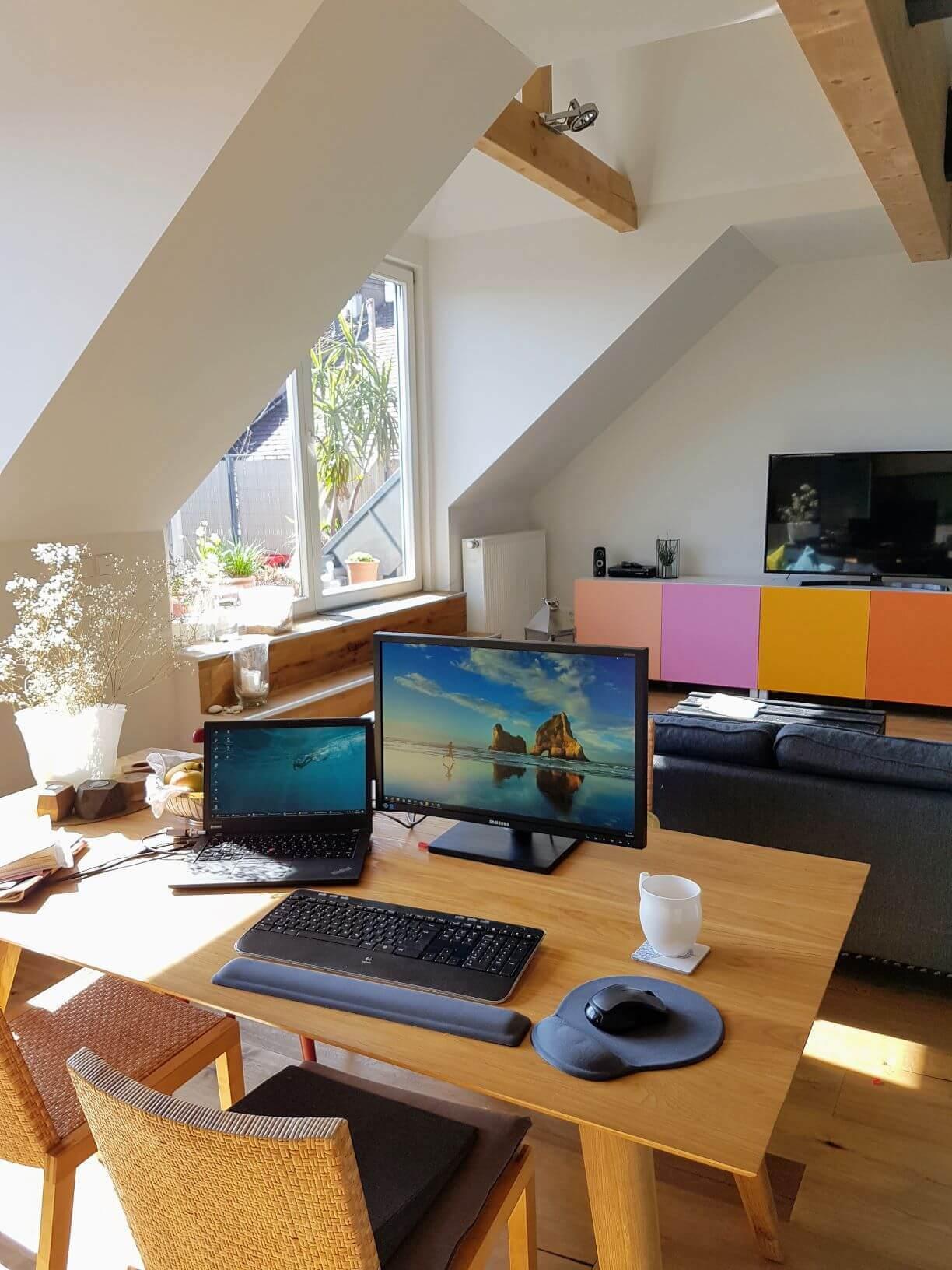 Home Office. Tisch mit Stühlen, auf dem Bildschirm und Laptop mit Tastatur und Maus stehen.