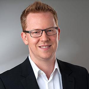 Porträt Mann mit Brille blickt lächelnd in die Kamera