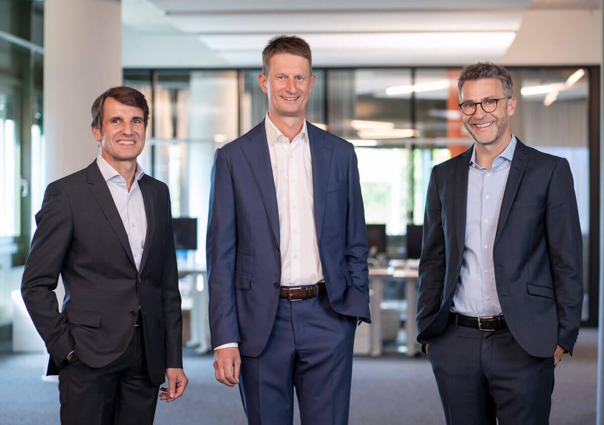 Unsere Geschäftsleitung. Drei lächelnden Männer in Anzügen in Büro