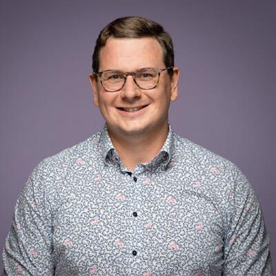 Lächelnder Mann mit gemustertem Hemd und Brille