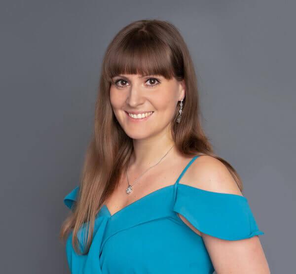 Lächelnde Frau in blauen Oberteil vor grauer Wand
